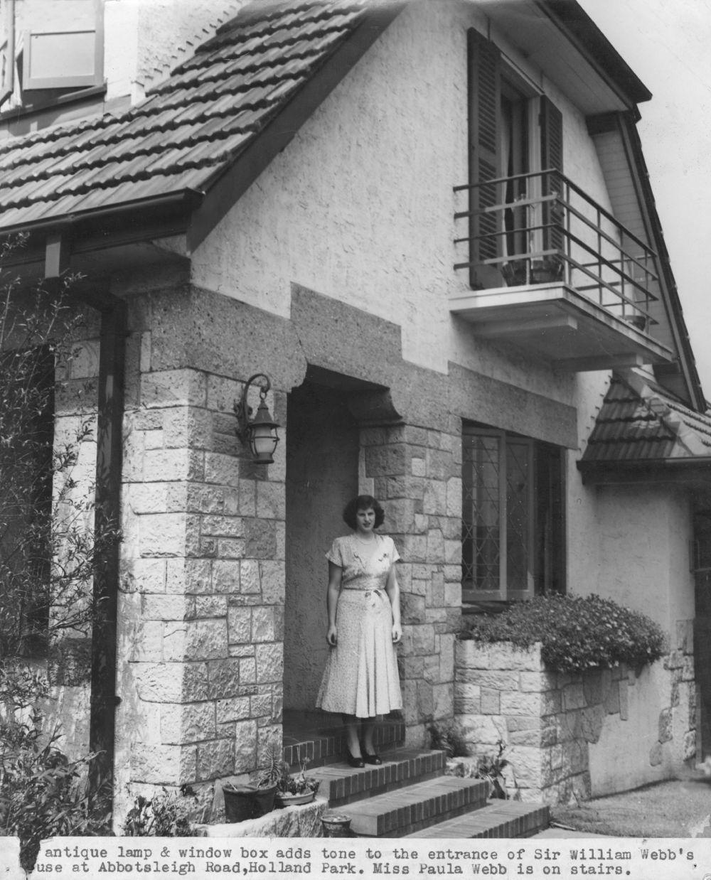 """This is an image of the Front entrance to the Webb family residence in Holland Park, 1948. the caption reads """"antique lamp & window box adds tone to the entrance of Sir William Webb's house at Abbotsleigh Road, Holland Park. Miss Paula Webb is on stairs"""""""